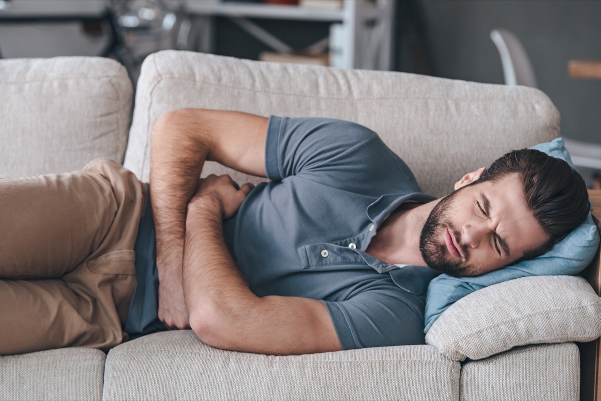 Man hugging his belly and keeping eyes closed while lying on the couch at home