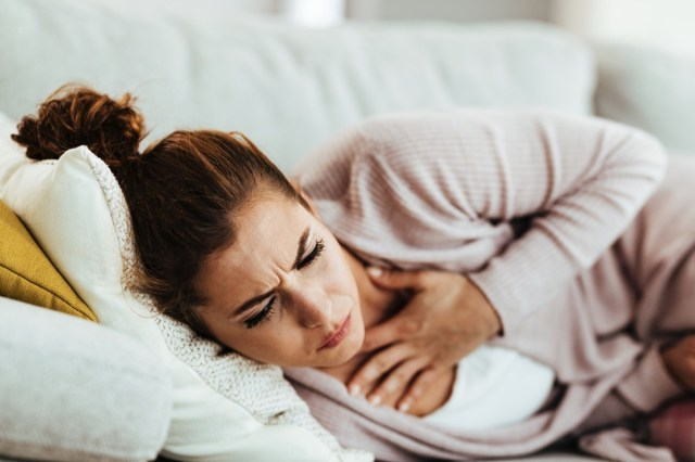 Woman having chest pain and coughing while lying down on sofa at home.