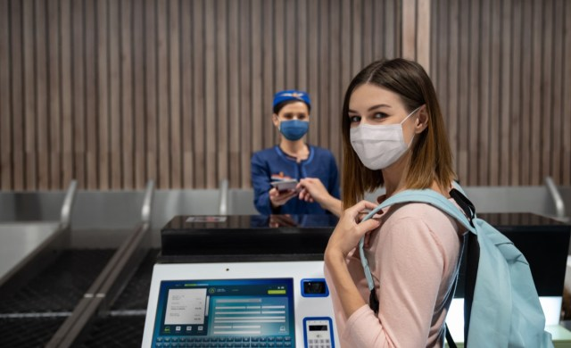 Traveling woman doing the check-in at the airport wearing a face mask.