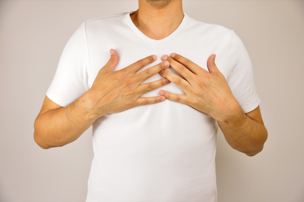 man with both hands on breast