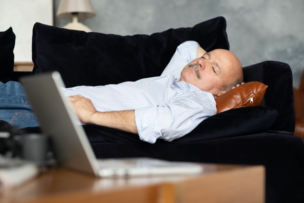 Tired senior hispanic man sleeping on dark blue couch, taking afternoon nap at the living room