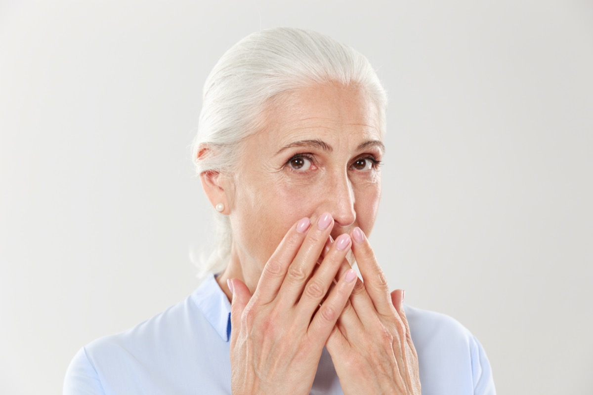 Close-up portrait of charming old lady, covering her mouth with hands