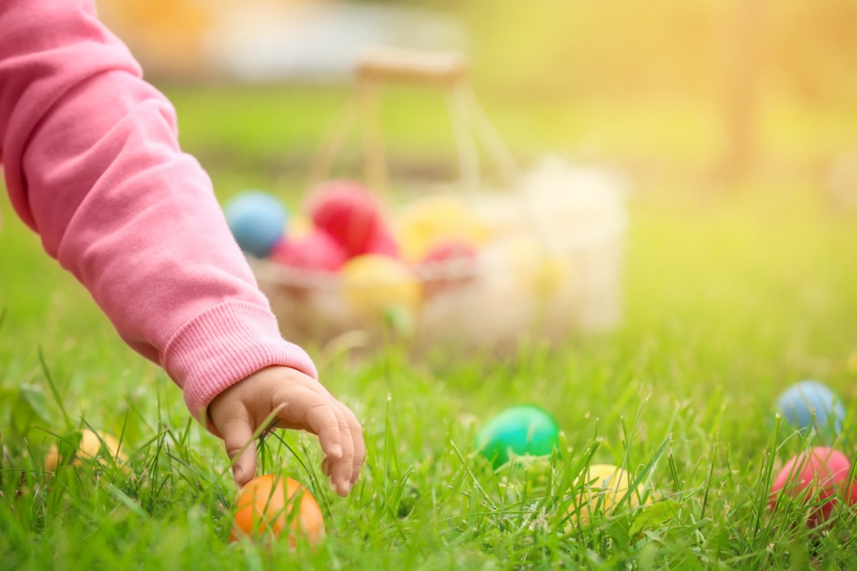 Little girl gathering colorful egg in park