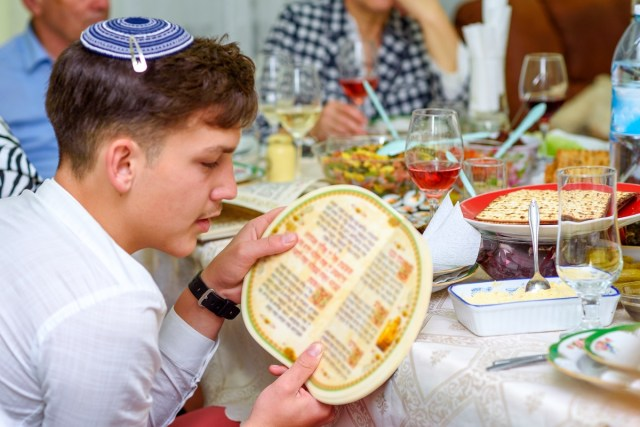 Jewish family celebrate Passover Seder reading the Haggadah