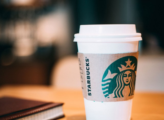 Starbucks cup of coffee at a table with a notepad