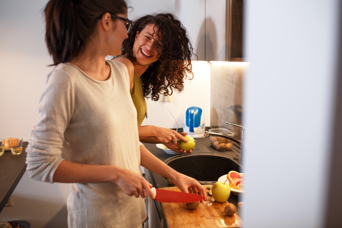 female friends in kitchen preparing together vegetarian meal