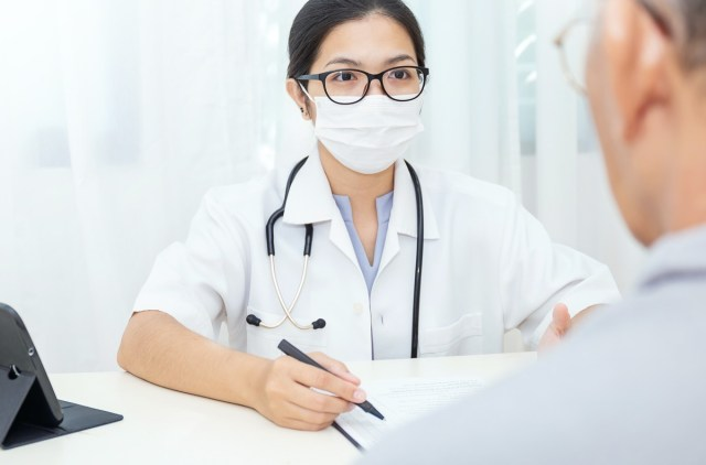 Portrait of asian woman doctor wear protection face mask showing a patient some information on digital tablet clip board, patient listen to specialist doctor in clinic office