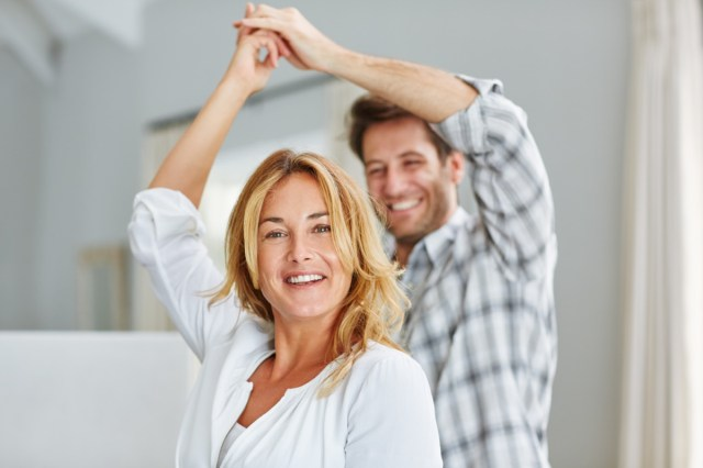 Smiling couple holding hands and dancing together at home