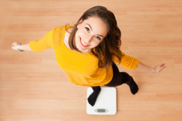 woman standing on a scale, happy about weight loss