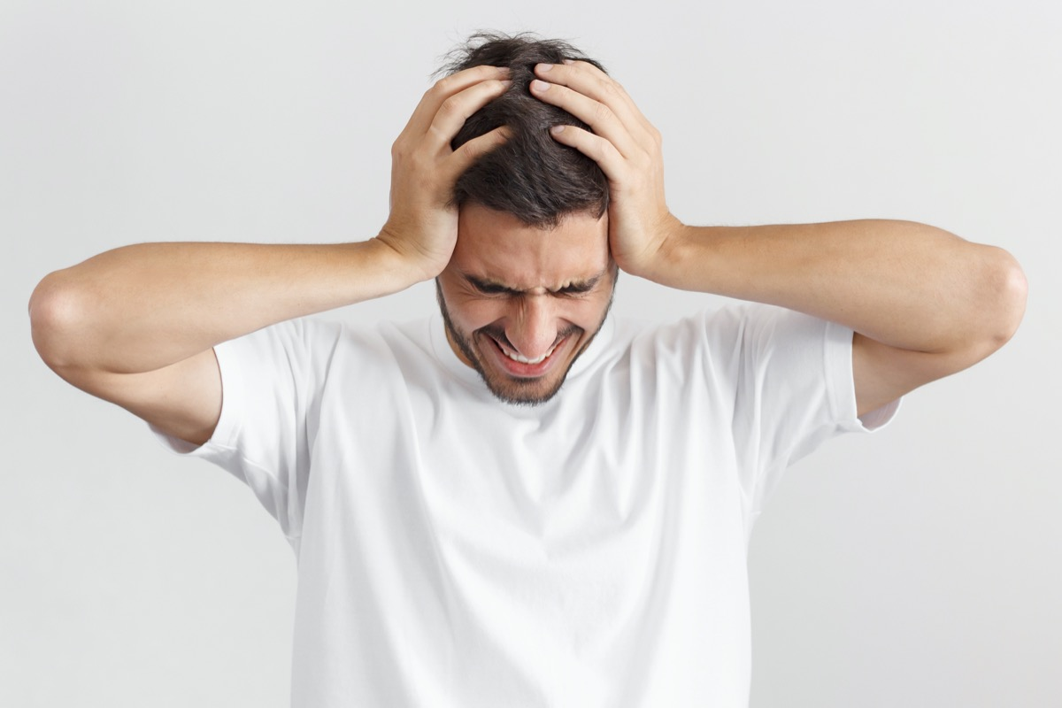 man in white casual t-shirt, holding head with both hands, suffering from severe headache