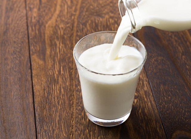 glass of milk being poured from glass jar