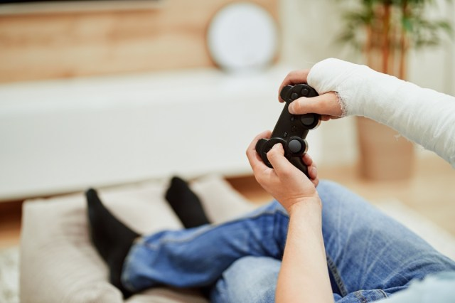Man with broken arm in plaster cast holding controller and playing in videogame in front of TV.