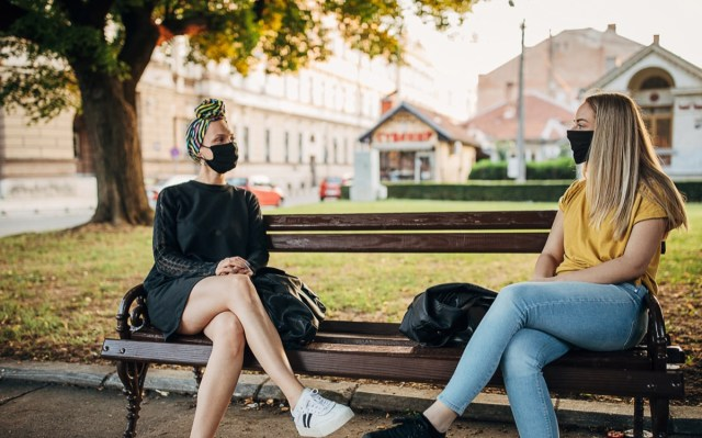 Two women with black face masks sitting on bench in park