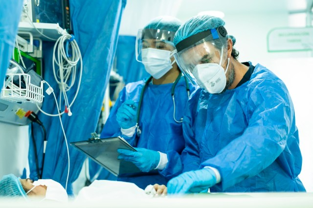 Pair of doctors checking an inpatient in intensive care while wearing their biosecurity suits