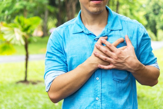 man holding hands on chest suffering from heart attack