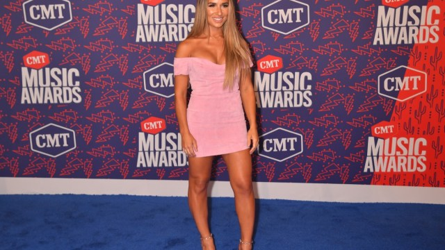 jessie james decker in pink dress in front of CMA step and repeat
