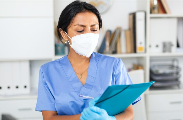 female doctor in surgical face mask meeting patient in medical office