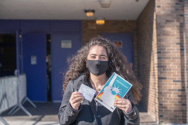A woman displays her vaccination card and the