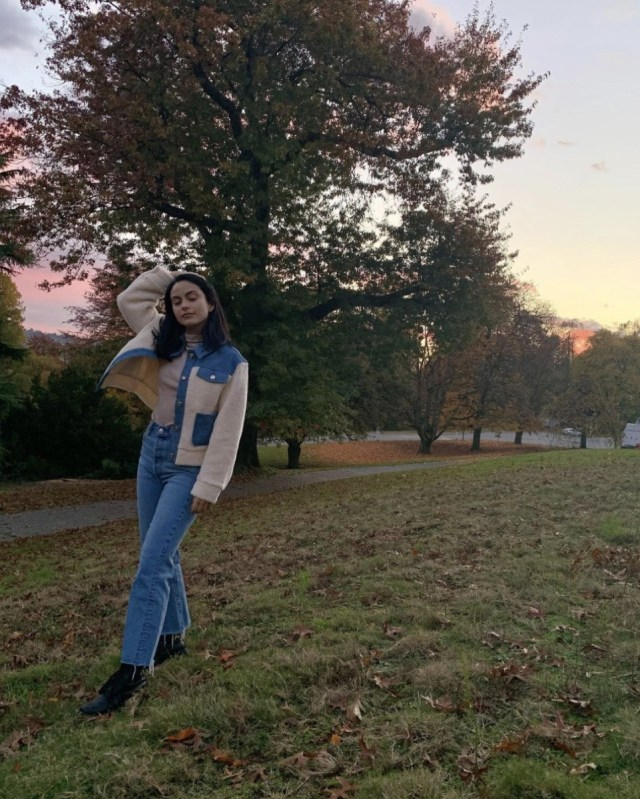 camila mendes posing in jeans and jacket outdoors