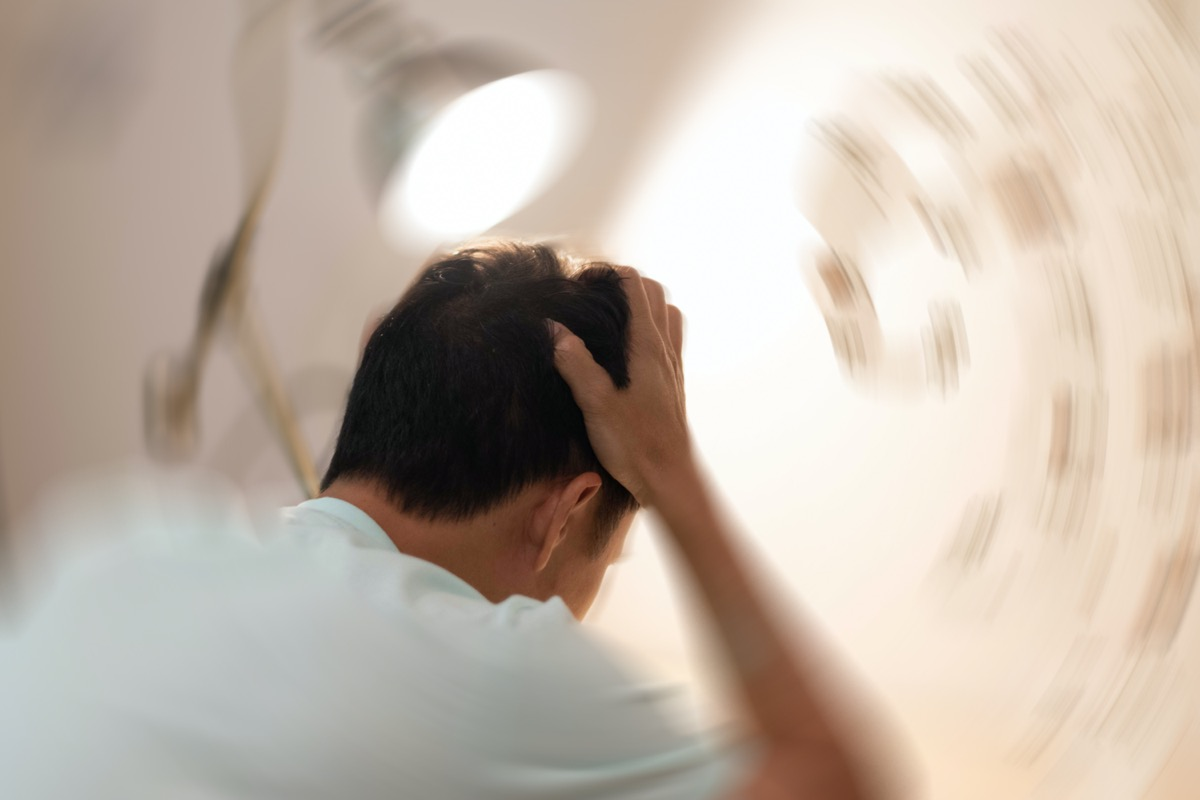 Man hands on his head felling headache dizzy sense of spinning dizziness,a problem with the inner ear, brain, or sensory nerve pathway