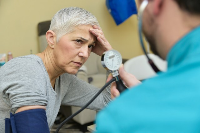 Senior lady receiving bad news about her blood pressure from her doctor