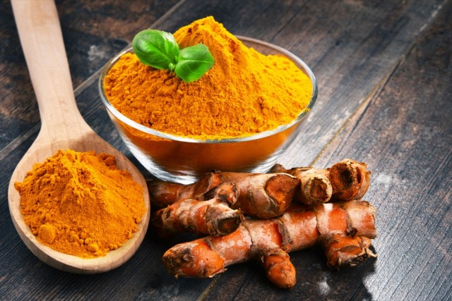turmeric in bowl and wooden spoon