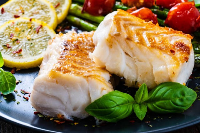 Fried cod fillet with asparagus on wooden table