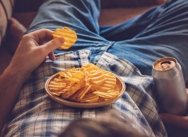 Bored guy lying down on couch eating potato chips and drinking a beer
