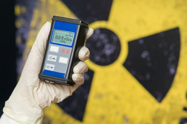 Radiation supervisor in glove with geiger counter checks the level of radiation in the radioactive zone.