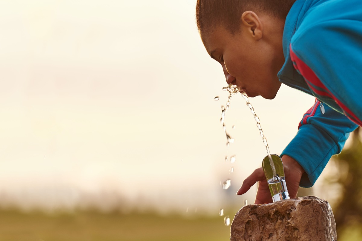 Close up image of a young mixed race girl busy drinking water from a fixed water fountain station with beautiful copy space