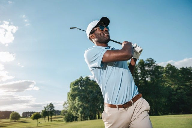 Smiling man man in cap and sunglasses playing golf