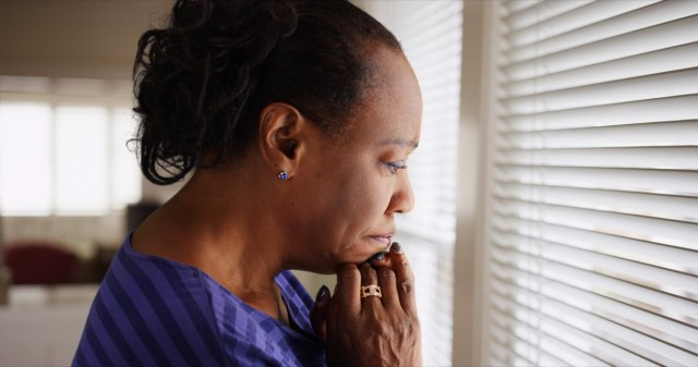 An older black woman mournfully looks out her window - Image