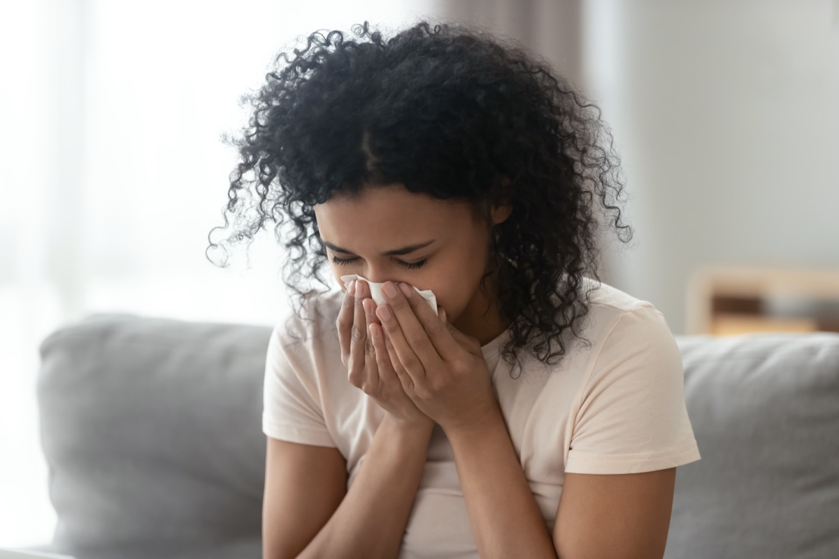woman blowing running nose got flu caught cold sneezing in tissue