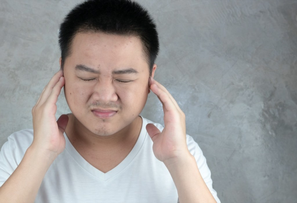 Asian men use hands to close their ears.