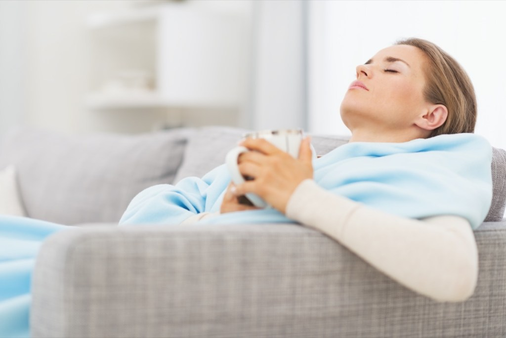 pills pack in hand of ill young woman laying on sofa.