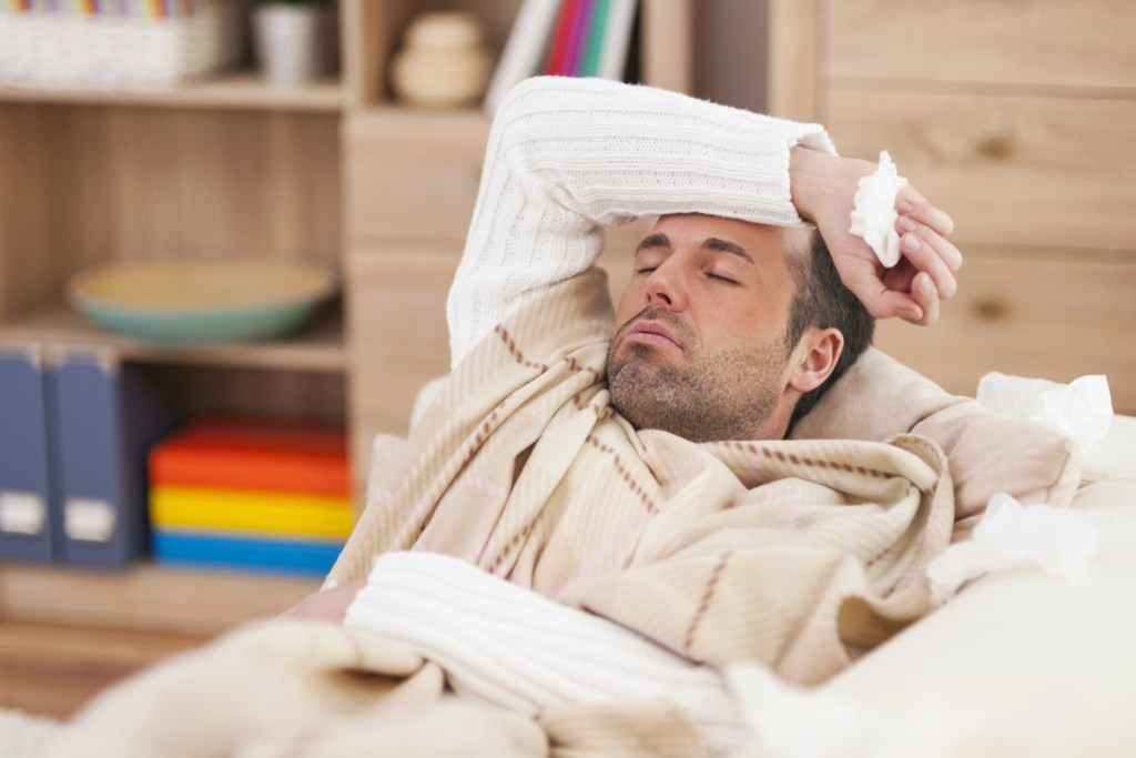 Sick man lying down on couch with high fever
