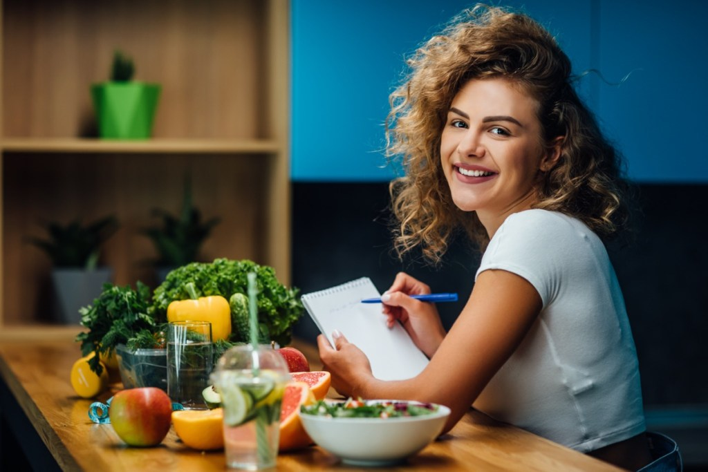 Nutritionist working in office. Doctor writing diet plan on table and using vegetables. Sport trainer