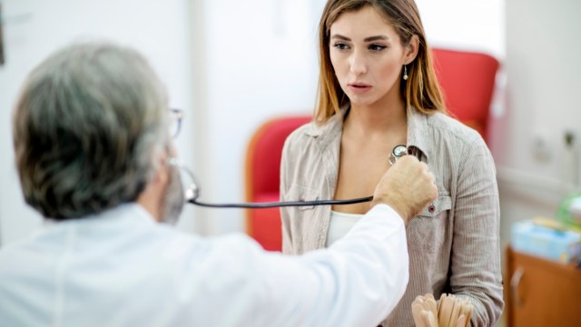Woman getting her painful chest examined by a doctor.