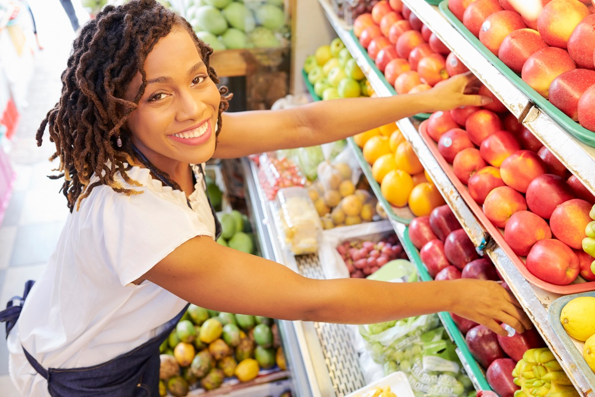 woman working at fruit department at grocery store