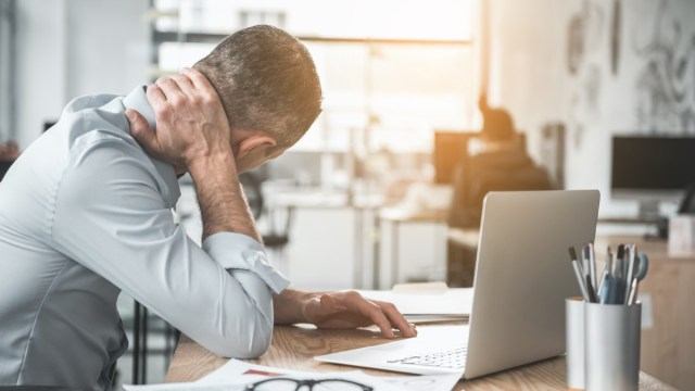 Man holding sore neck while using notebook