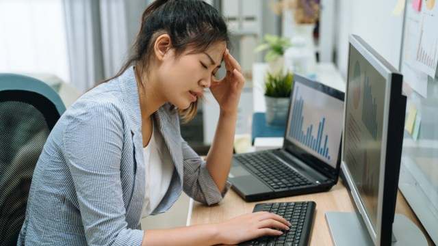 Stressed frustrated young asian businesswoman reading bad email internet news on computer feeling sad tired