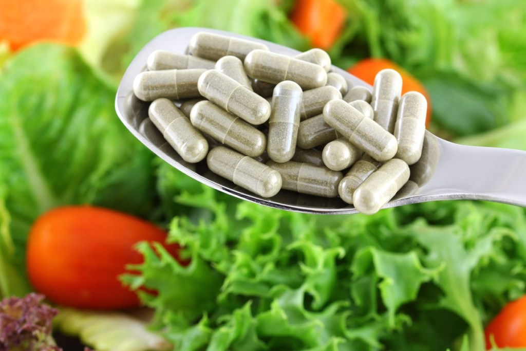 A spoon of concentrated Fiber Capsules with Fresh vegetable Salad background