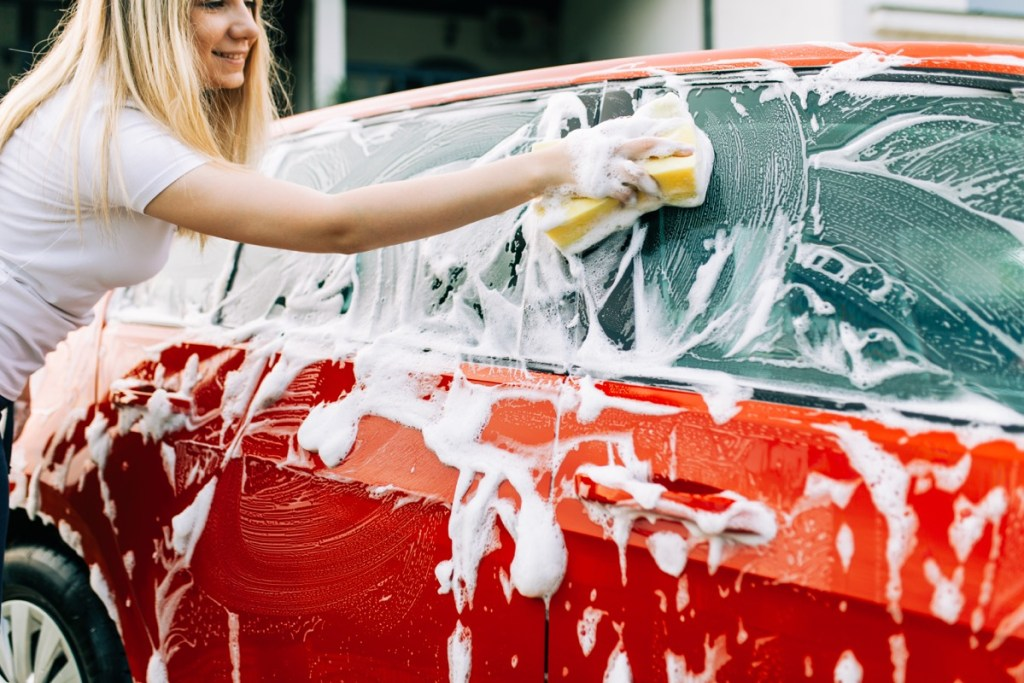 woman washing her car with sponge