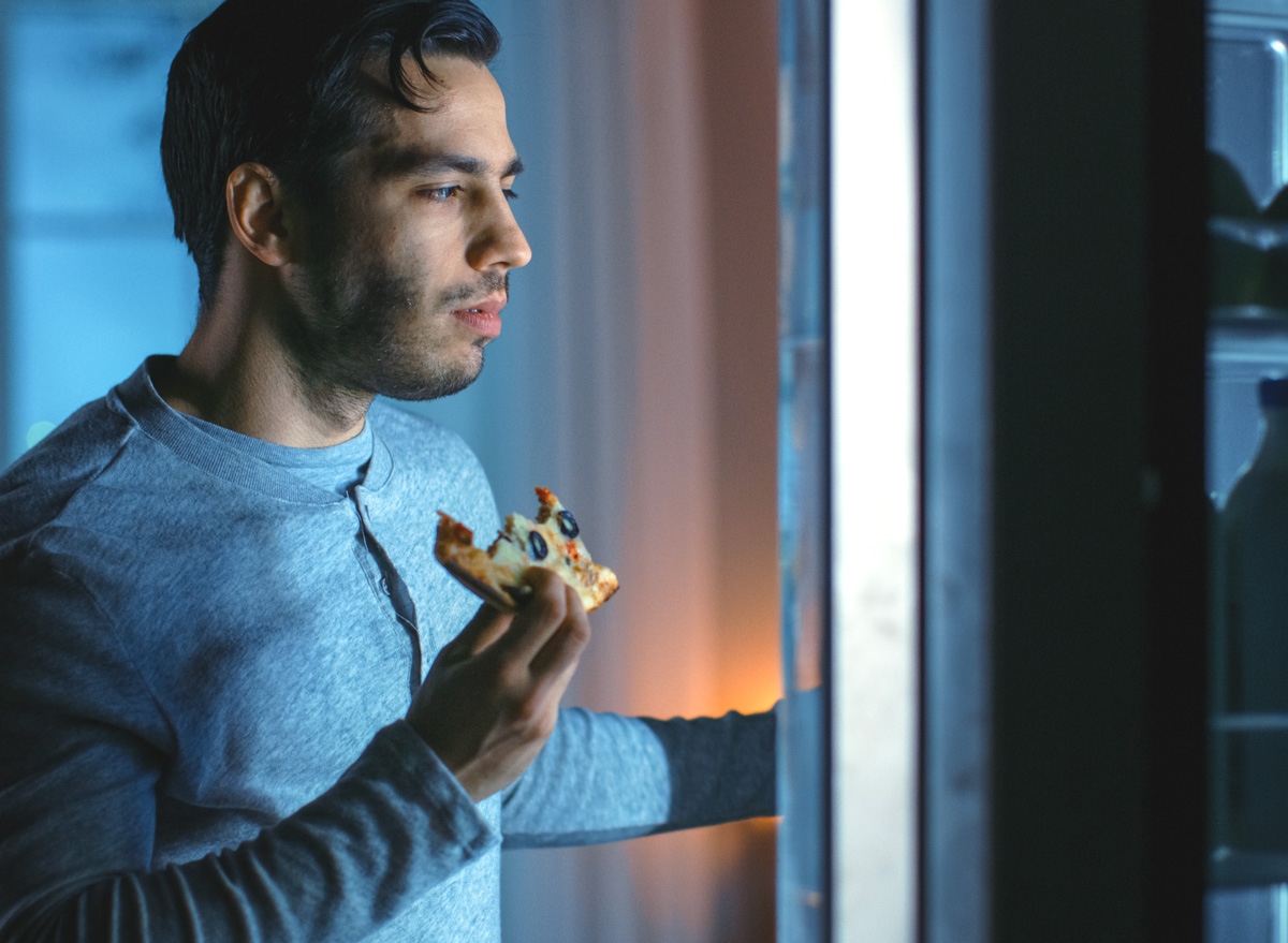 man eating leftover pizza as a late night snack