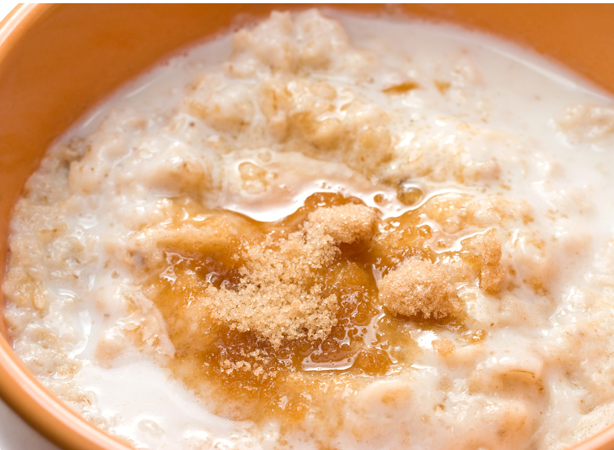 Bowl of oatmeal with brown refined sugar and milk
