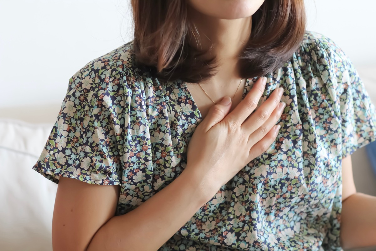 Woman in the casual wear raise her hand over her heart.