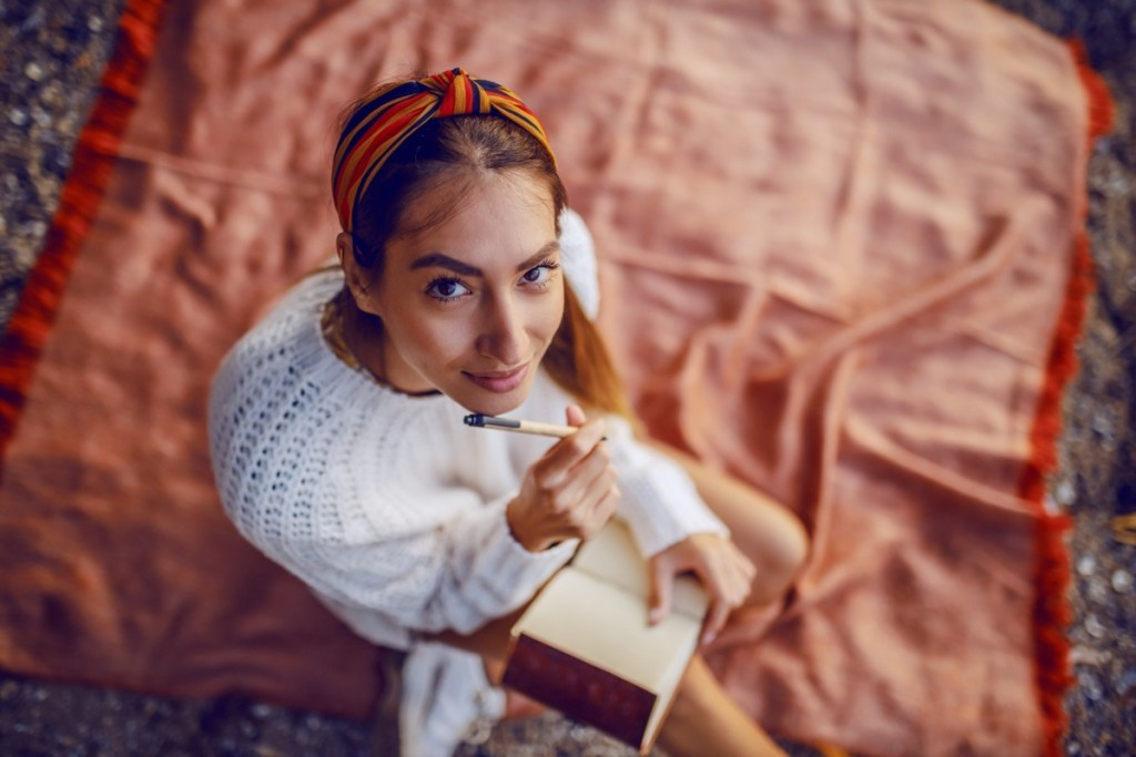 Top view of caucasian brunette in sweater and with headband sitting on blanket outdoors and holding pen and diary in hands while looking at camera.