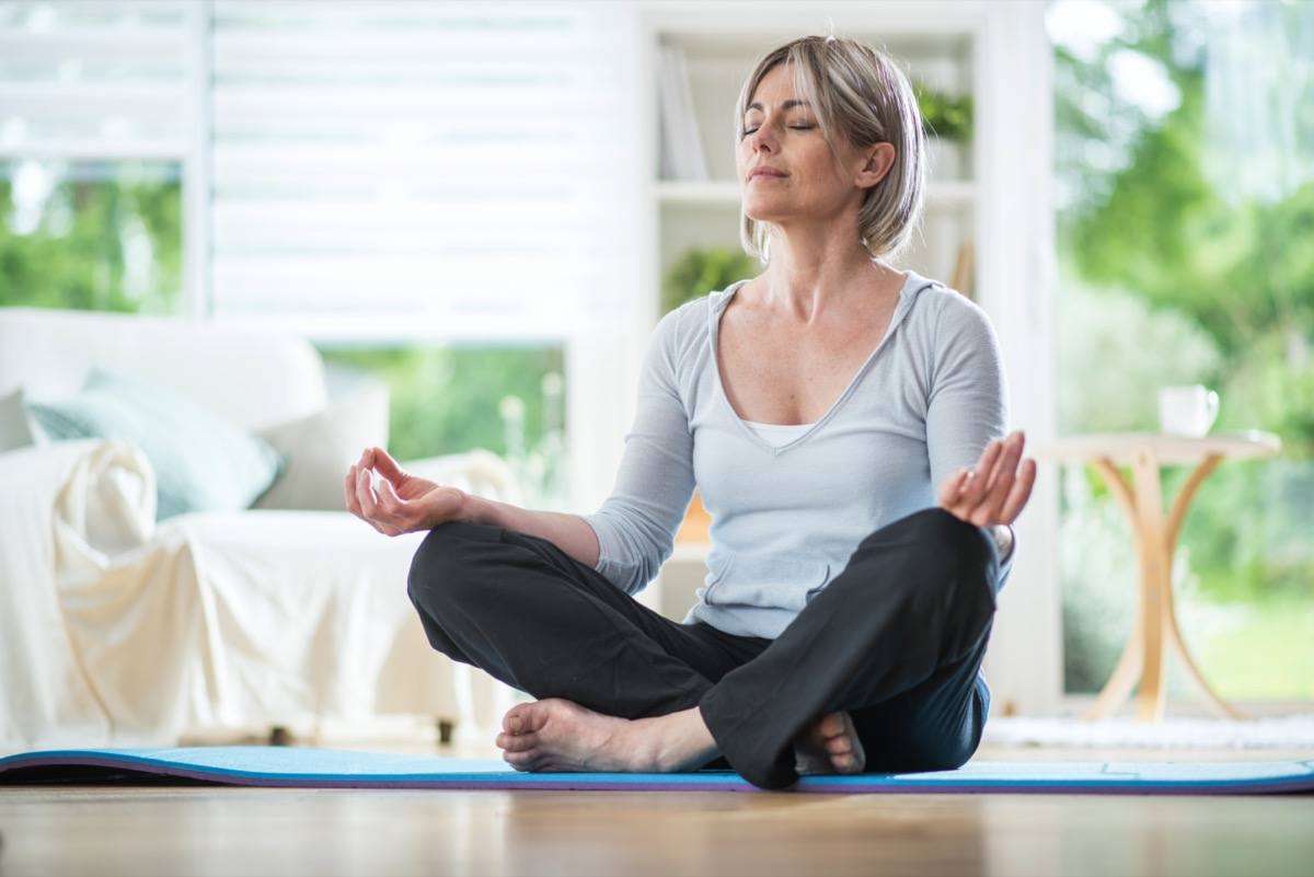 Middle aged woman sitting in lotus position on a carpet in his living room. her eyes are closed. she is in the foreground