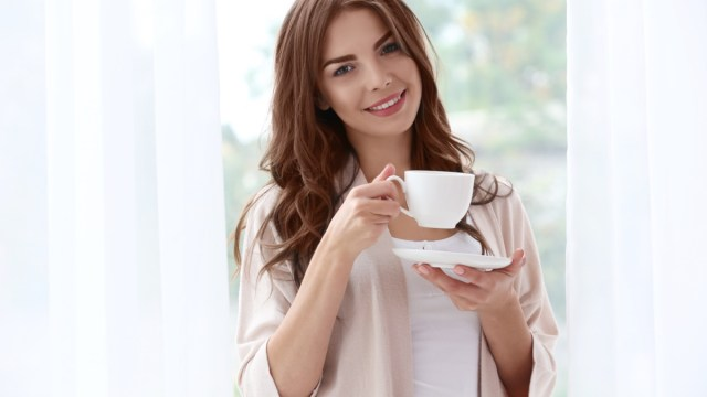 Woman holding a cup of coffee standing near window.