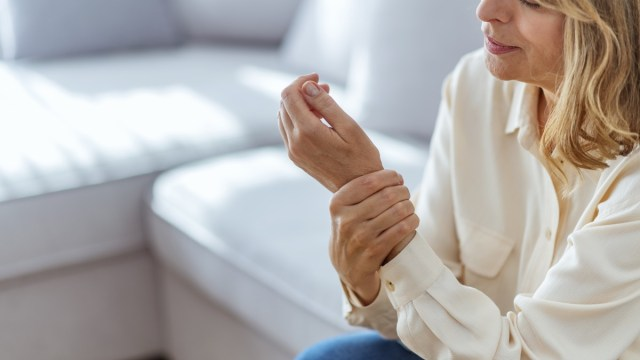 Senior woman suffering from pain in hand at home.